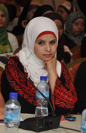 Amaal Zamaareh  listening to the Minister of National Economy's speech during the Youth Summit