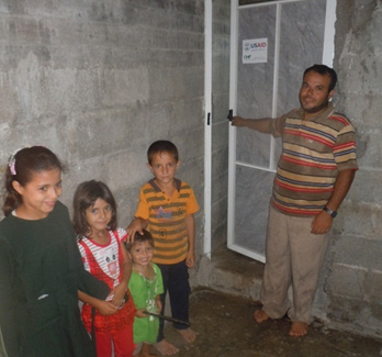 Khaled and four of his children stand with their new door